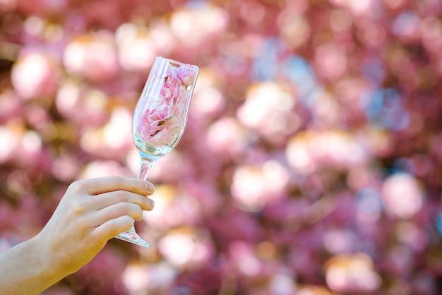 Frau, die ein glas mit rosa blütenblättern von sakura hält.