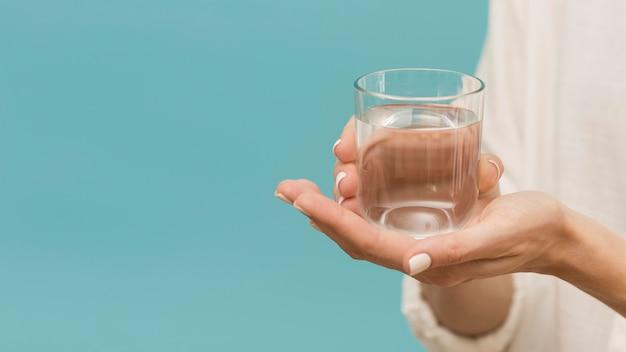 Frau, die ein glas mit wasserkopierraum gefüllt hält