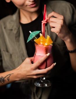 Frau, die ein glas rosa cocktail mit orangenscheiben garniert hält