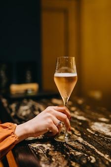 Frau, die ein glas rosenchampagner an einem restaurant auf bartheke hält.
