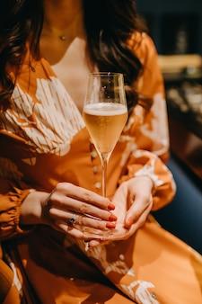 Frau, die ein glas rosenchampagner an einem restaurant hält.