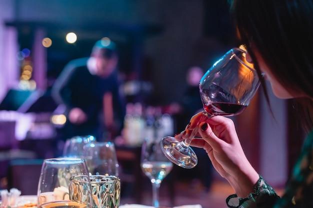 Frau, die ein glas rotwein hält. abendessen im restaurant, party