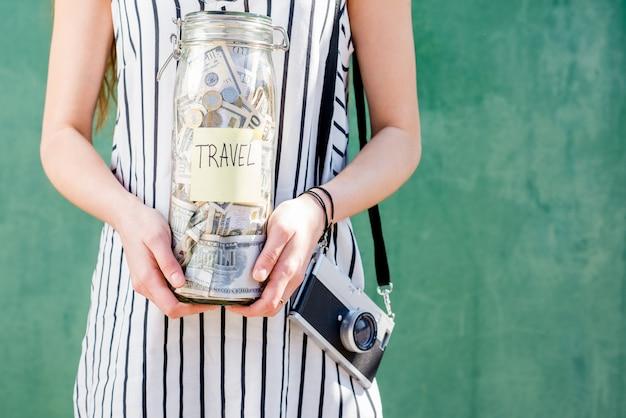 Frau, die ein glas voller geld für das reisen hält, das mit fotokamera auf dem grünen hintergrund steht. geld sparen für sommerferienkonzept