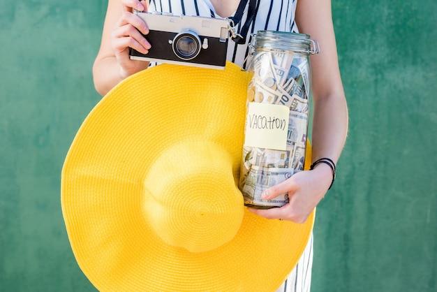 Frau, die ein glas voller geldeinsparungen für den sommerurlaub mit gelbem hut und fotokamera auf grünem hintergrund hält
