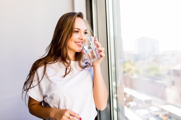 Frau, die ein glas wasser hält, während sie aus dem fenster schaut - rückseite der schattenbildfrau