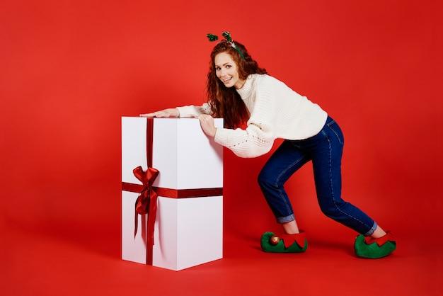 Frau, die ein großes weihnachtsgeschenk trägt