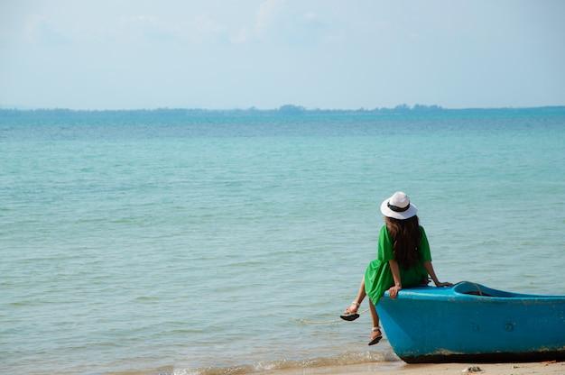 Frau, die ein grünes hemd trägt, einen weißen hut trägt und auf einem boot sitzt, das am strand geparkt ist.
