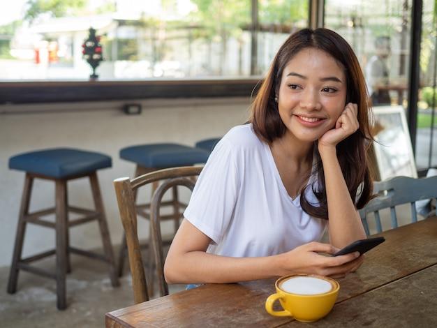 Frau, die ein handy in einem café verwendet