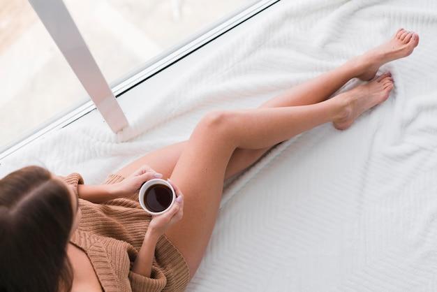 Frau, die ein hemd trägt und tasse kaffee hält