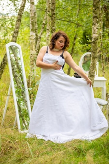 Frau, die ein hochzeitskleid vor dem spiegel im wald anprobiert
