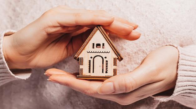 Frau, die ein hölzernes haus mit ihren händen mit der sonne auf einem hellrosa hintergrund hält. süßes zuhause