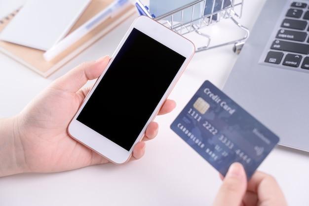 Frau, die ein intelligentes mobiltelefon für das einkaufen der elektronischen zahlung hält
