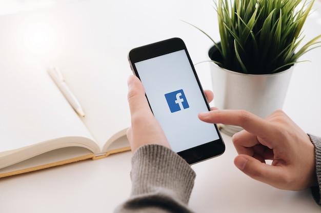 Frau, die ein iphone 6s mit sozialinternet-service facebook auf dem schirm hält