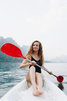 Frau, die ein kanu durch einen nationalpark schaufelt