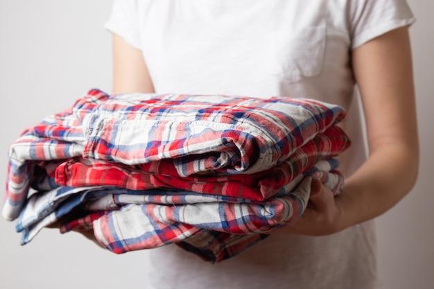 Frau, die ein kariertes hemd hält