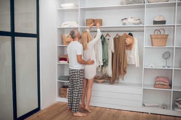 Frau, die ein kleid in einem kleiderschrank wählt und ihrem ehemann zeigt
