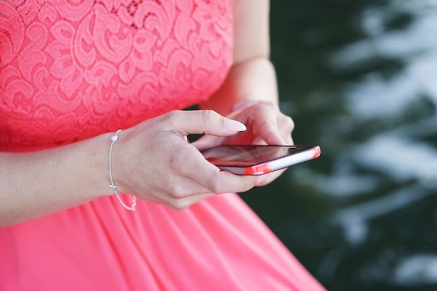 Frau, die ein kleid trägt und ein smartphone hält