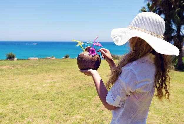 Frau, die ein kokosnusscocktail trinkt