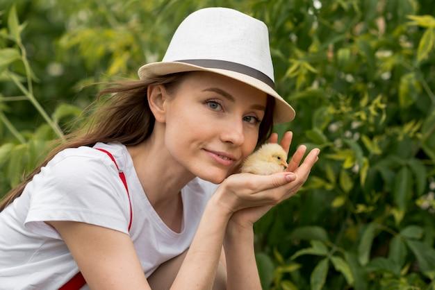 Frau, die ein küken auf einem bauernhof hält