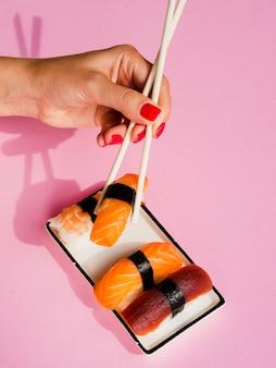 Frau, die ein lachssushi von der platte mit sushi nimmt