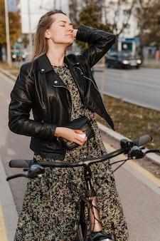Frau, die ein langes kleid hält, das ihre fahrradvoransicht hält