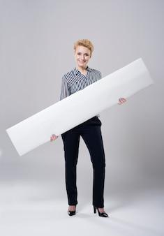 Frau, die ein langes weißes plakat trägt