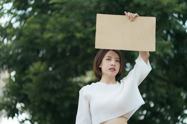 Frau, die ein leeres banner hält, um den text auf protest zu setzen.