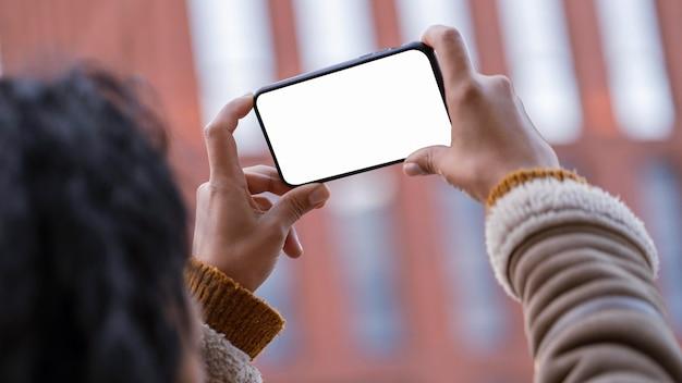 Frau, die ein leeres bildschirm-smartphone draußen betrachtet