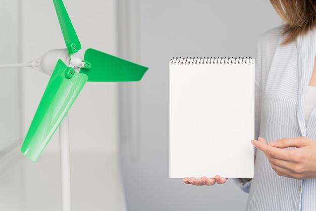 Frau, die ein leeres notizbuch zu einer windkraftinnovation zeigt