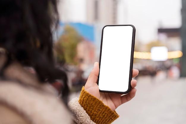 Frau, die ein leeres smartphone draußen hält
