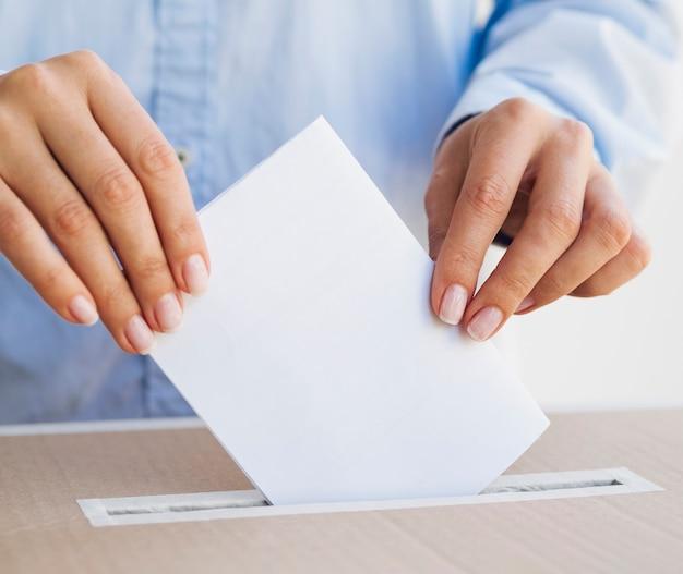 Frau, die ein leeres stimmzettelmodell hält