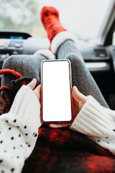 Frau, die ein leeres telefon im auto hält