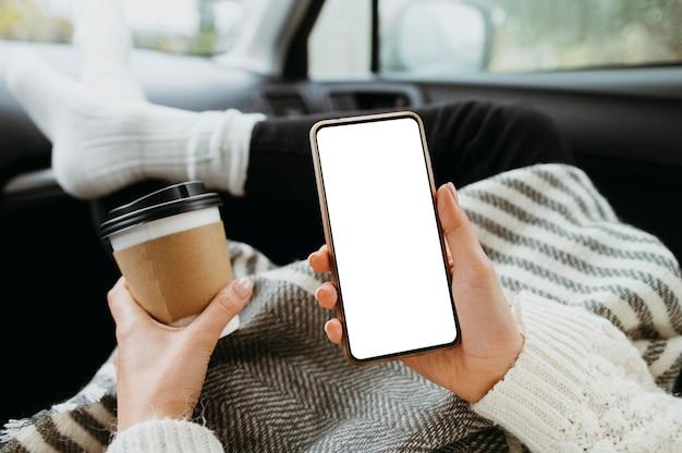 Frau, die ein leeres telefon und eine tasse kaffee hält