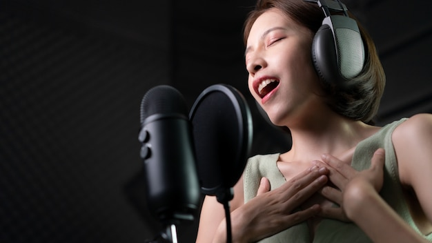 Frau, die ein lied oder ein geschichtenerzählen im studio aufzeichnet.