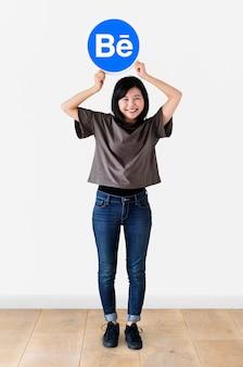 Frau, die ein logo von behance hält