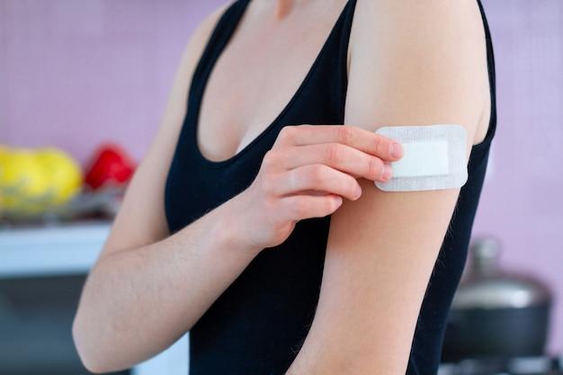 Frau, die ein medizinisches heftpflaster für verletzten finger verwendet. erste pflaster für schnitte und wunden