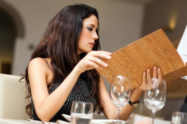 Frau, die ein menü im restaurant betrachtet