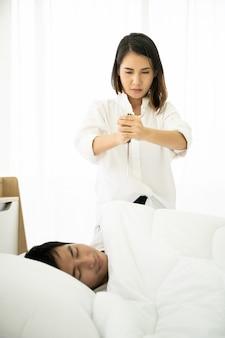 Frau, die ein messer hält und auf ihren ehemann das schlafen auf dem bett zielt. konzept des familienproblems und der scheidung.