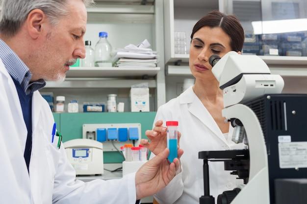 Frau, die ein mikroskop in einem chemischen labor verwendet