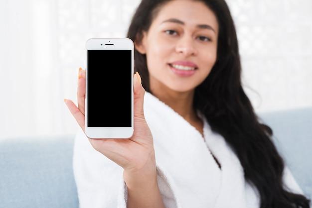 Frau, die ein mobile in einem badekurort verwendet
