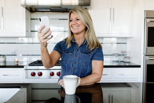 Frau, die ein mobiltelefon in der küche benutzt