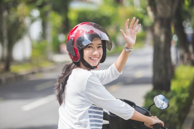 Frau, die ein motorrad reitet und hand winkt