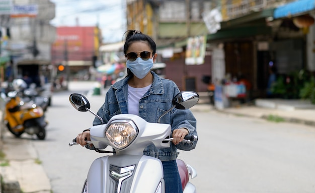 Frau, die ein motorrad trägt, das eine maske in der stadt trägt