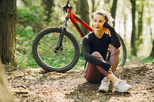 Frau, die ein mountainbike im wald reitet