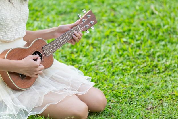 Frau, die ein nettes weißes kleid trägt und ukulele spielt