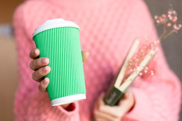Frau, die ein offenes buch mit einem blumenstrauß von getrockneten blumen nach innen und einer pappbecher kaffee hält