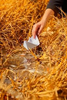 Frau, die ein origami-boot ins wasser setzt.