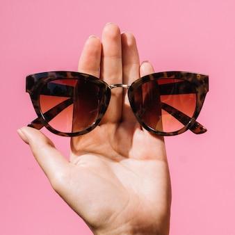 Frau, die ein paar modebrillen hält