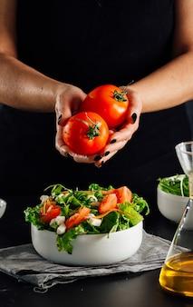 Frau, die ein paar tomaten hält, um sie dem salat hinzuzufügen, um gegessen zu werden