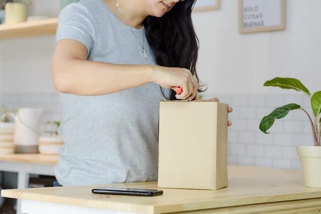 Frau, die ein paket mit cutter öffnet